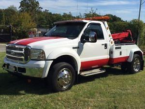 A red and white tow truck sitting on the lawn
