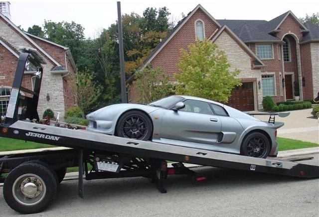 A flat deck tow truck hauling away a new grey sports car