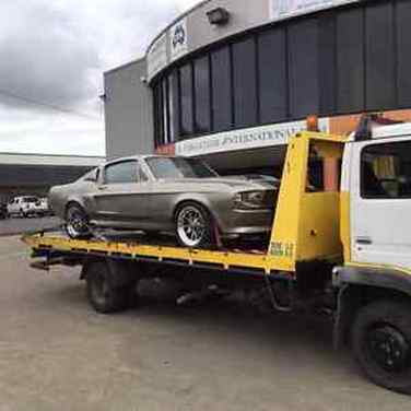 A new grey Ford Mustang on the back of a flat deck tow truck