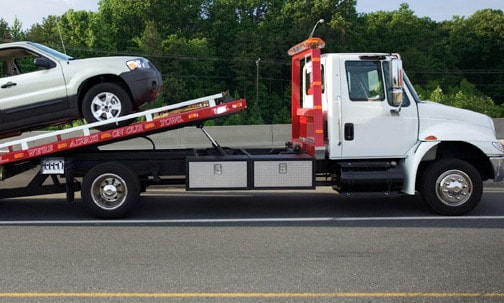 A flat bed tow truck loading a vehicle from the side of the highway