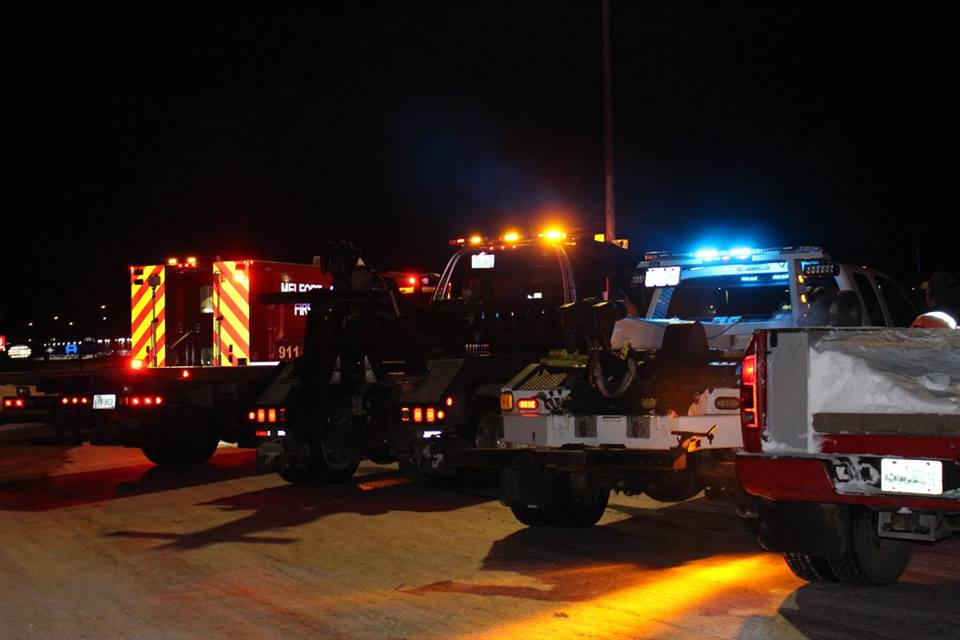 A night time picture of two tow trucks and a fire rescue vehicle participating in a rally or safety for tow truck operators