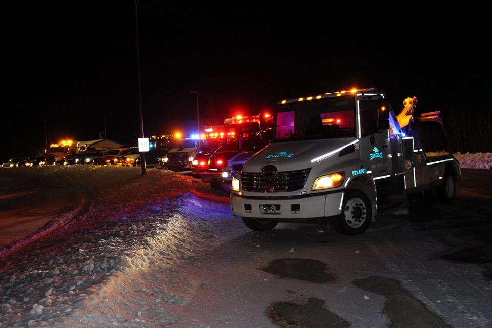 A picture at night of a bunch o tow trucks and other emergency vehicles for a rally or a fallen tow truck driver