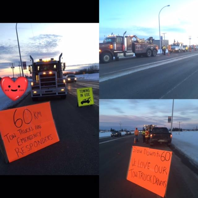 A bunch of tow trucks parked on the side of the highway with homemade signs asking people to slow down to 6o KMS while passing.