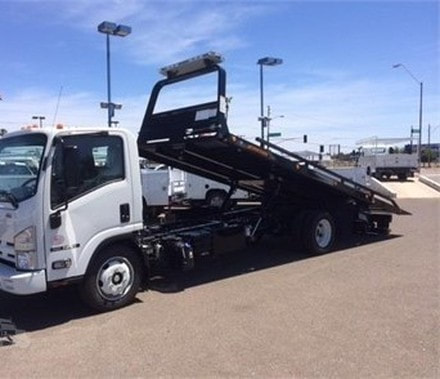 A new flat deck tow truck with is ramp tilted back in a car dealership parking lot